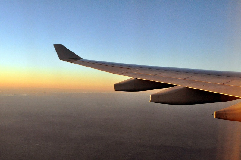 Airplane wing over sunset