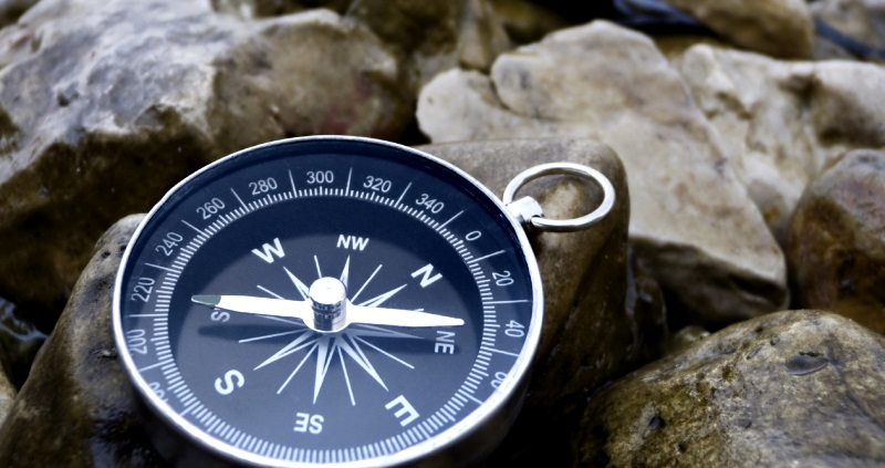 Compass on rocks with water