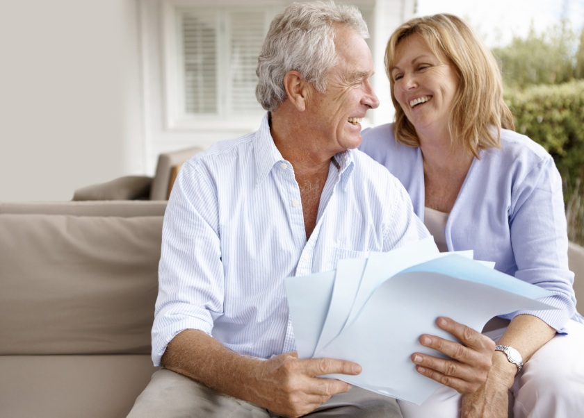 Elderly couple laughing with paperwork