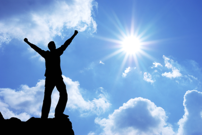 Silhouette of man celebrating in sunlight