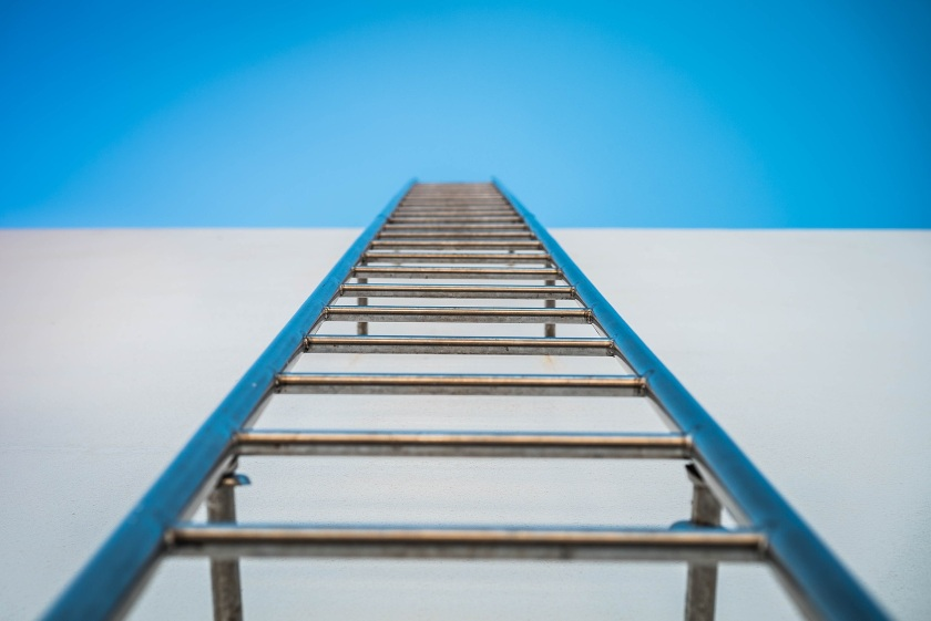 Ladder facing upwards into blue sky