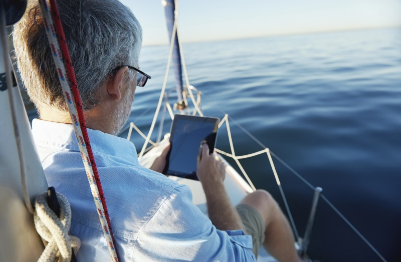 man-ipad-boat-blue-water