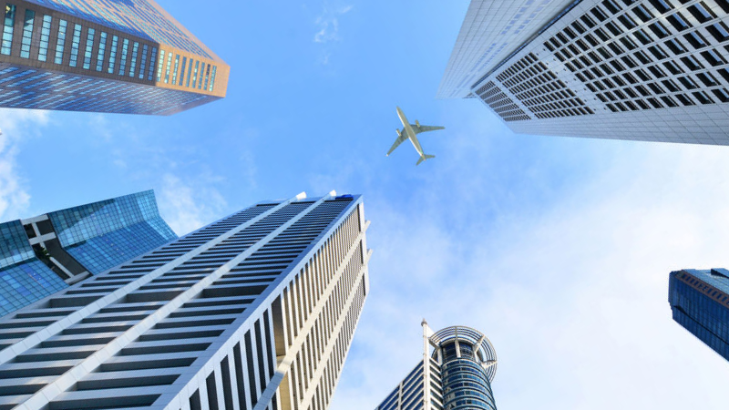 plane flying over buildings